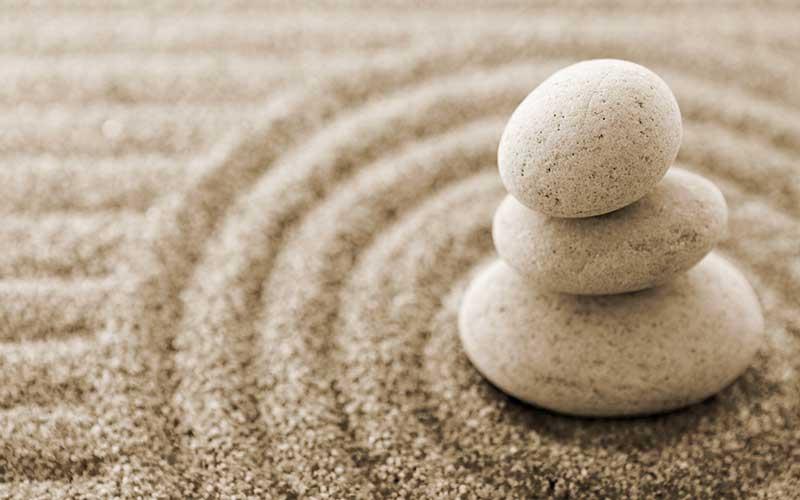 tre sassi sovrapposti sulla sabbia