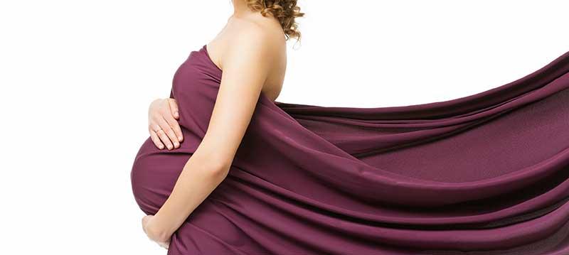 donna con il pancione avvolta in un telo amaranto
