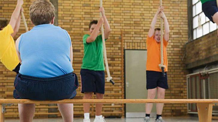 un bambino obeso siede su una panca in palestra mentre gli altri fanno ginnastica
