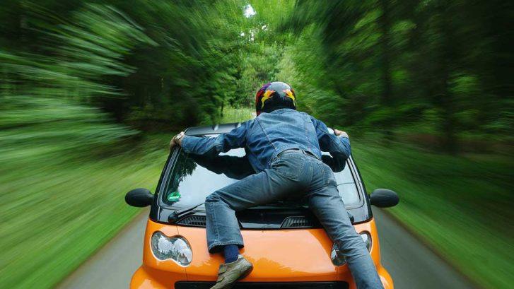 un pilota con tuta e casco è aggrappato al cofano di una macchina in corsa