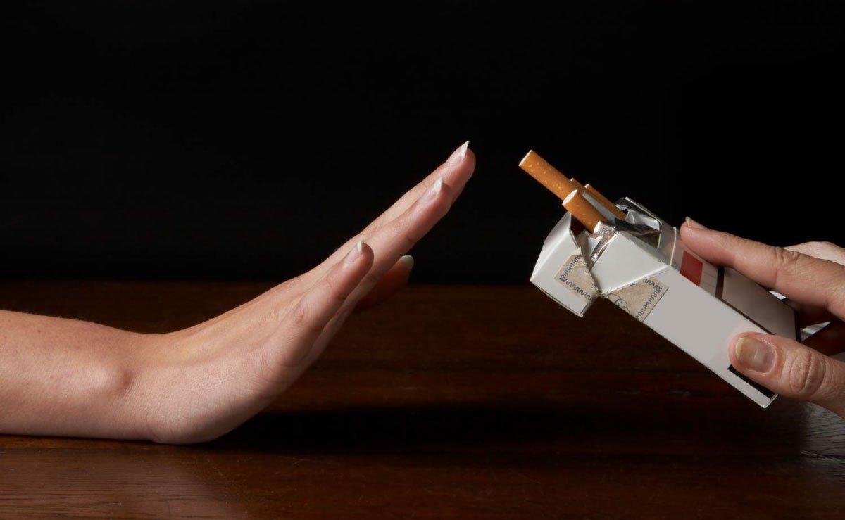 una mano ferma rifiuta un pacchetto di sigarette