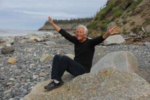 un anziano sorride felice a braccia aperto seduto su uno scoglio