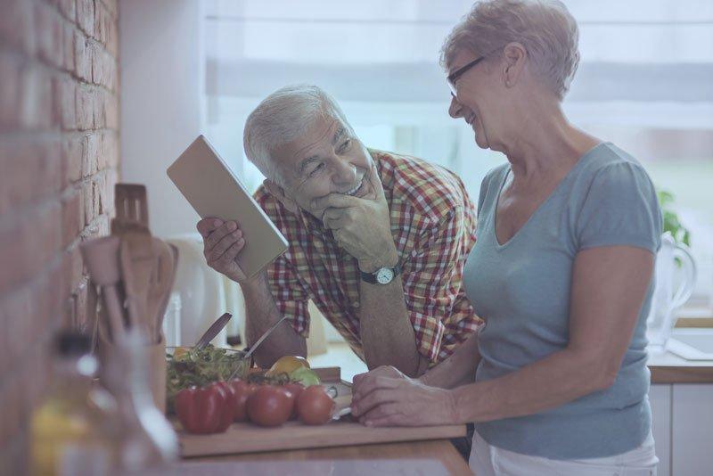 due anziani sorridono l'un l'altro mentre preparano del cibo