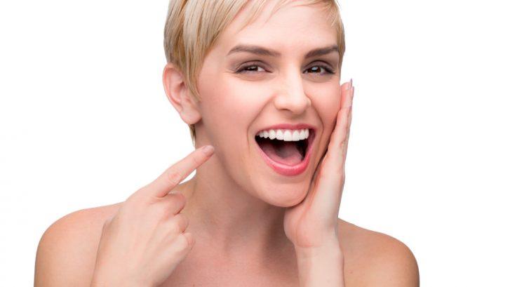 Immagine di una ragazza sorridente che indica la sua perfetta dentizione