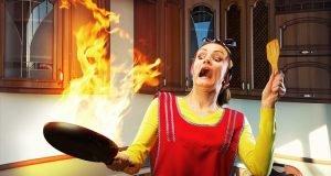 una donna spaventata tiene a distanza una padella che ha preso fuoco