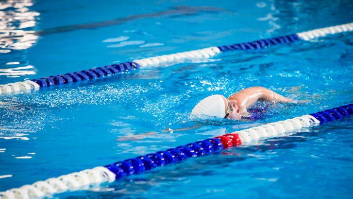 una bambina nuota in una piscina al chiuso