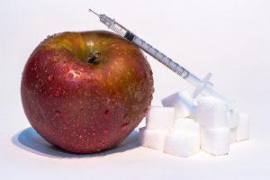 una mela, una siringa e delle zollette di zucchero