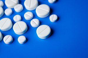 immagini di pillole di aspirina su sfondo blu
