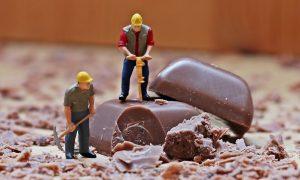 miniature di operai lavorano sopra due quadretti di cioccolata