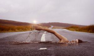 immagine illusoria di una donna che sembra nuotare su una strada di cemneto