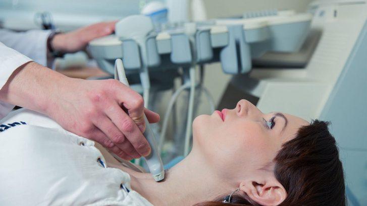 un medico sta facendo un'ecografia tiroidea ad una paziente