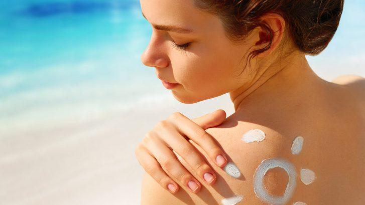 Una ragazza sulla spiaggia si mette la crema da sole