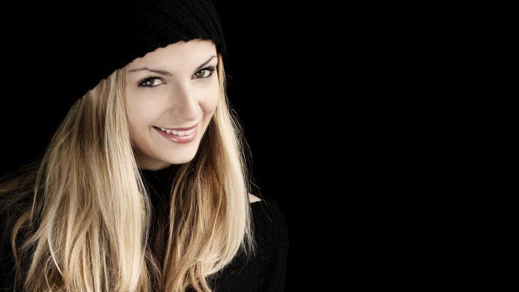 Una ragazza bionda sorride mostrando una dentatura perfetta
