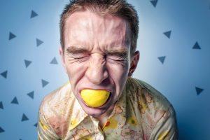uomo con un limone in bocca strizza gli occhi per l'acidità