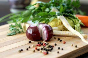 una cipolla tagliata a metà su un tagliere assieme ad altre verdure