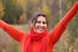 Una donna vestita di rosso sorride felice a braccia alzate