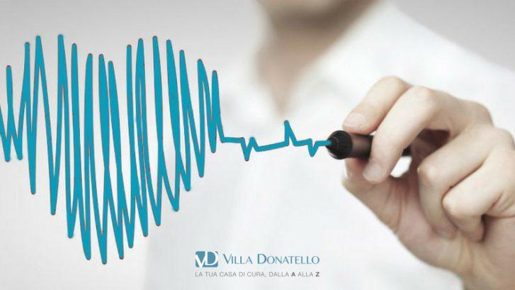 una mano disegna su un vetro un cuore azzurro