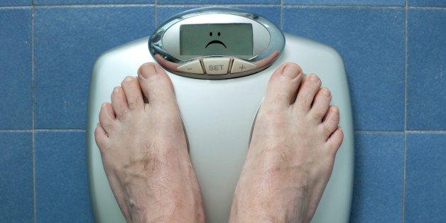due piedi su una bilancia che invece di restituire un peso fa la faccina triste