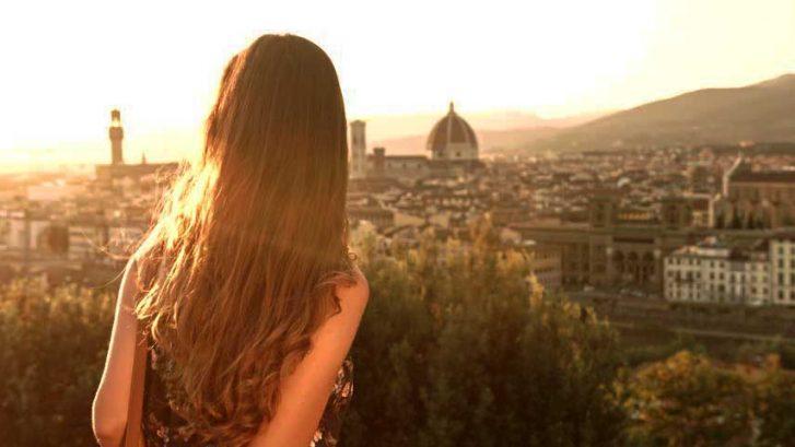 Una ragazza di spalle guarda un panorama di Firenze