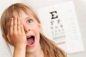 Una bambina si tappa un occhio sorridente durante una visita oftalmologica