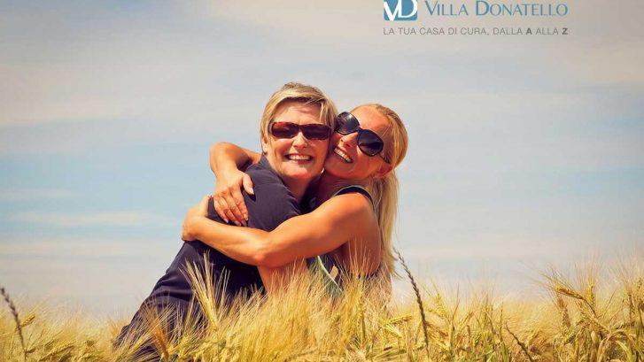 due donne si abbracciano allegre in un campo di grano