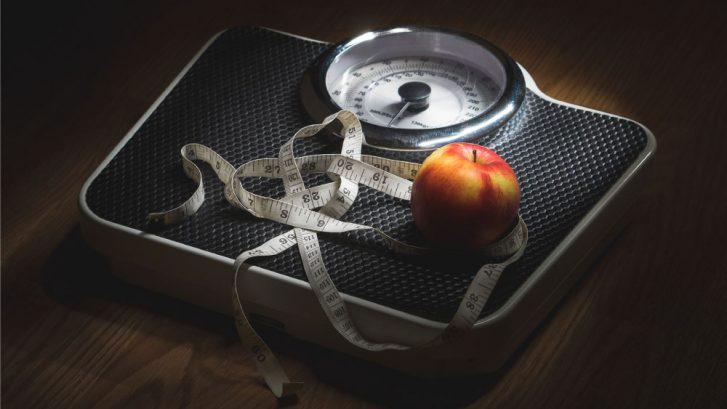 una bilancia in penombra con un metro da sarto e una mela sopra