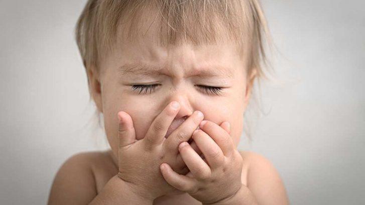 Un bambino si tiene le mani davanti alla bocca mentre sta tossendo