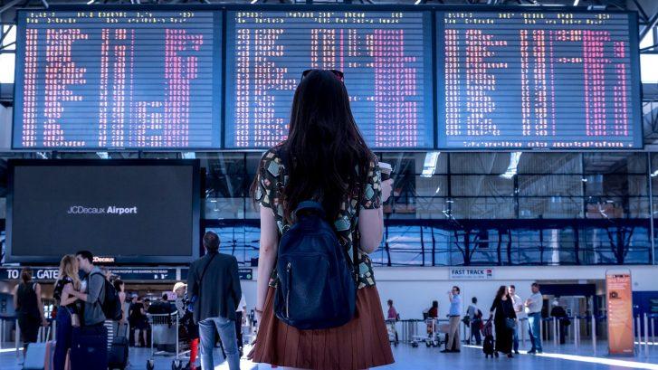 una ragazza in piedi, in aeroporto, di fronte ai display degli orari di partenze e arrivi