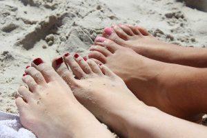 due coppie di piedi sulla sabbia