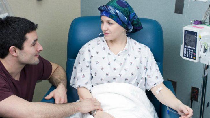 una donna in un letto di ospedale sta affrontanto la chemioterapia con il supporto del proprio compagno a fianco