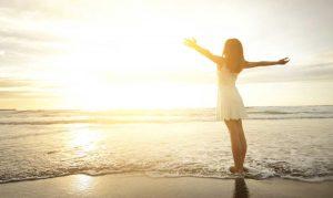 una ragazza in riva al mare allarga le braccia per godersi gli ultimi raggi di sole