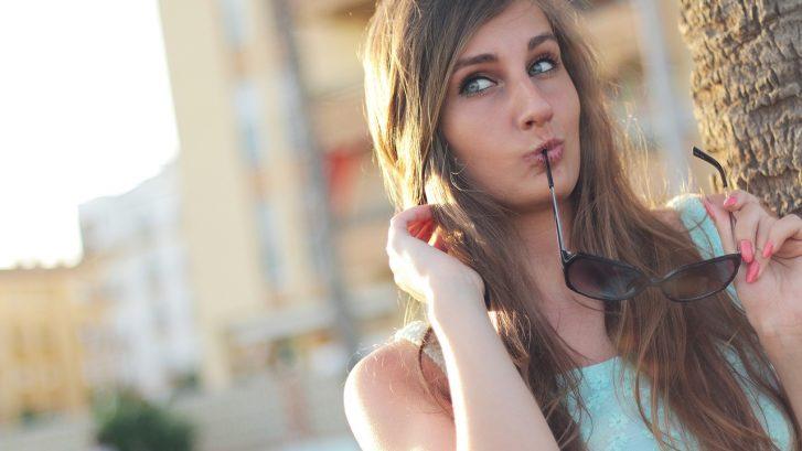 una ragazza tiene in bocca gli occhiali