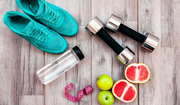 scarpe sportive, pesi e frutta fresca
