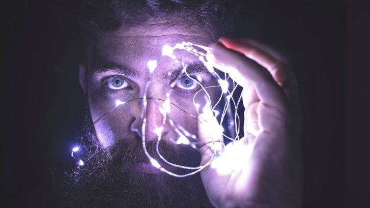 un uomo co una folta barba è illuminato da una fila di led viola