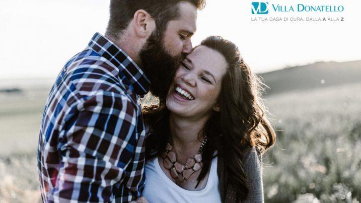 un ragazzo con folta barba bacia una ragazza sulla guancia
