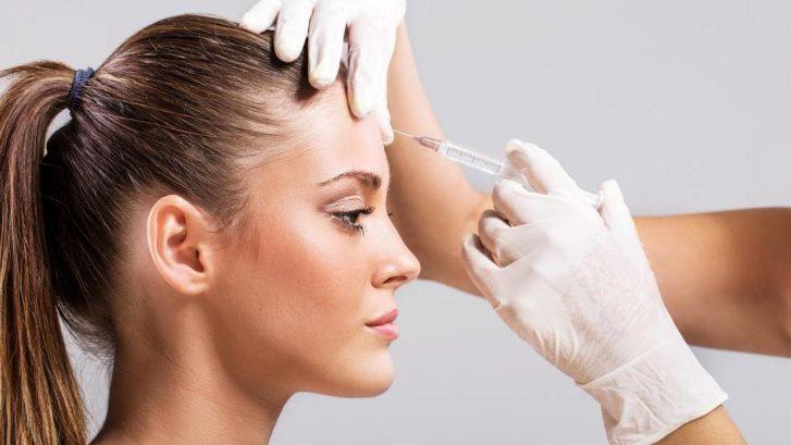 un medico sta effettuando un'iniezione di botulino sulla fronte di una ragazza