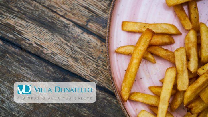 Un piatto di patatine fritte appoggiato su un tavolo di legno scuro