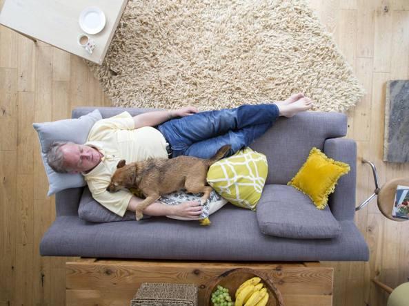 un uomo dorme sul divano abbracciato al suo cane