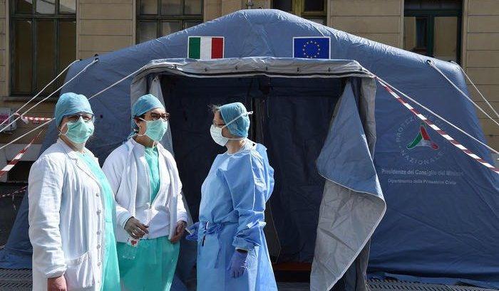 Tre medici con tute e mascherine di fronte ad una tenda da triage