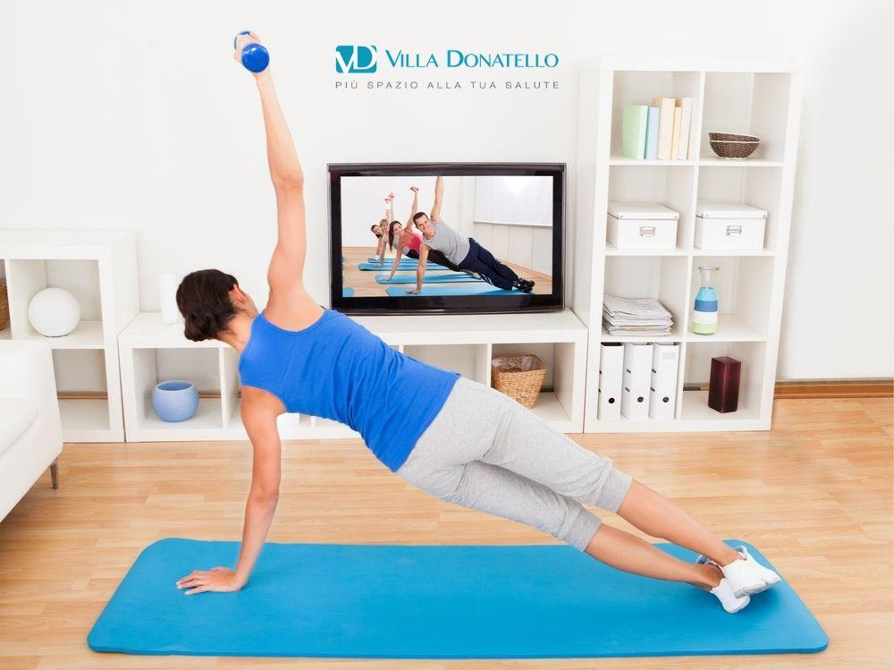 una ragazza fa esercizio fisico in casa guardando la televisione