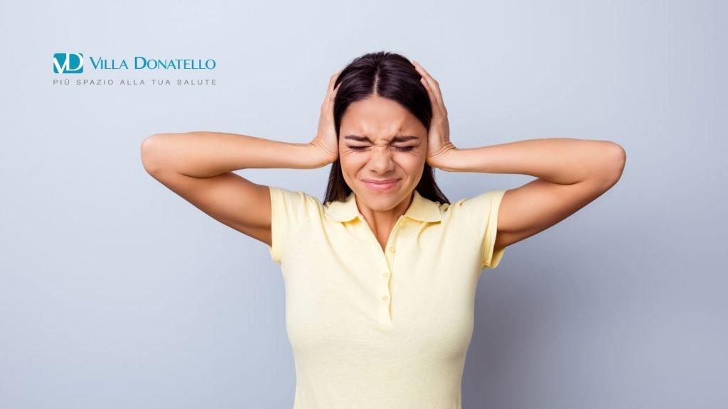 Una donna si tappa le orecchie chiaramente infastidita da un rumore
