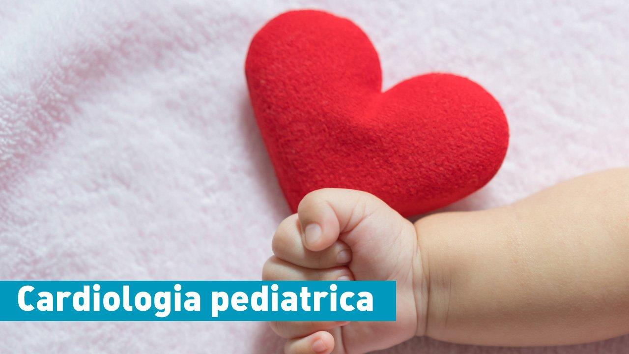 la mano di un neonato accanto a un piccolo cuore in tessuto