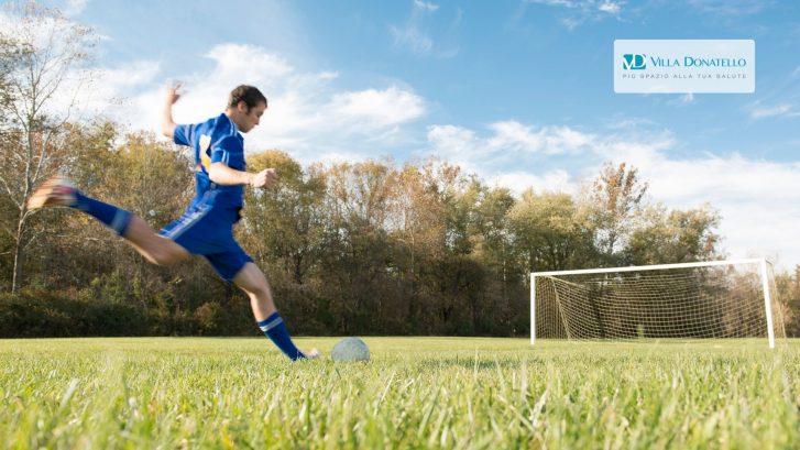 un ragazzo sta per calciare un pallone in porta su un campo di calcio