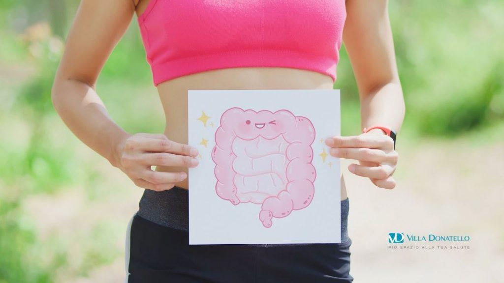 una donna tiene all'altezza dell'addome un cartello con il disegno dell'intestino