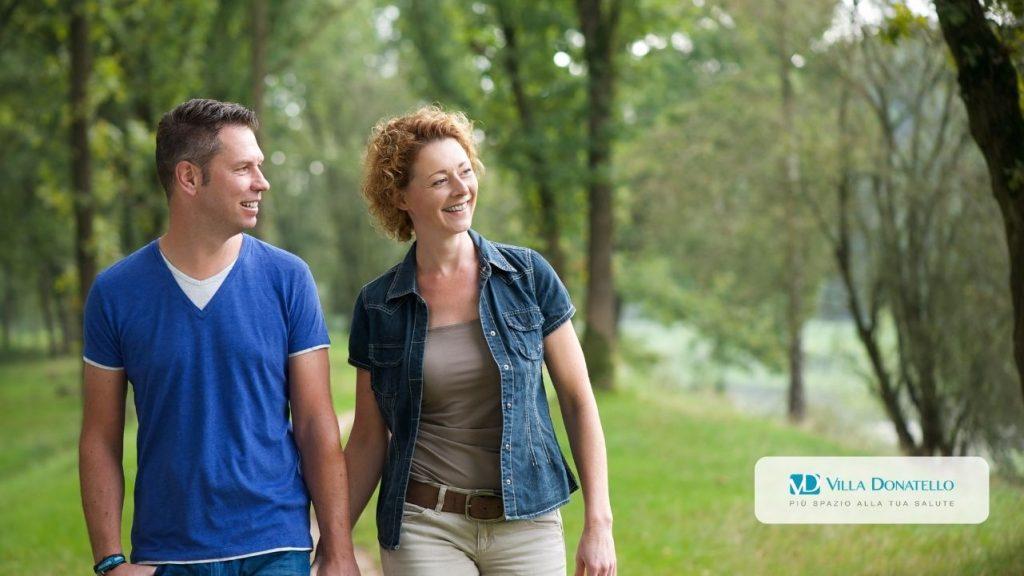 Un uomo e una donna camminano nel verde di un parco mano nella mano