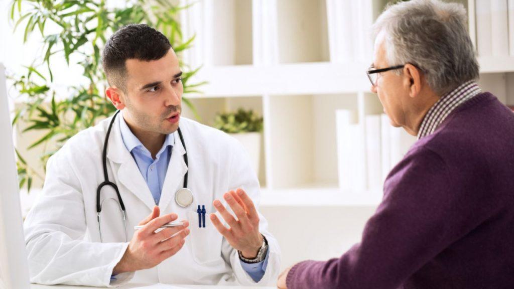 Un medico parla con un paziente anziano