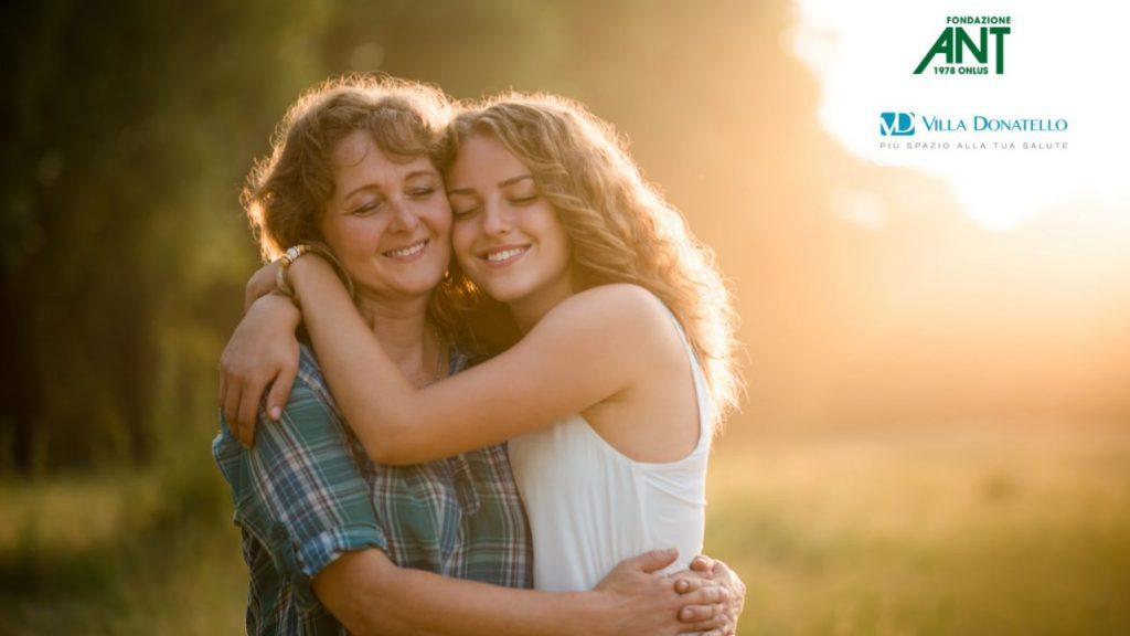 una madre e una figlia si abbracciano al tramonto